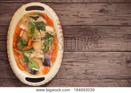 Rustic jellied fish in oval dish on old table. Top view with copy space