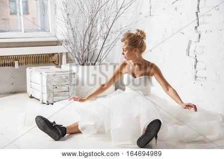 Beautiful sexy blonde girl in white dress and boots posing near the white wall