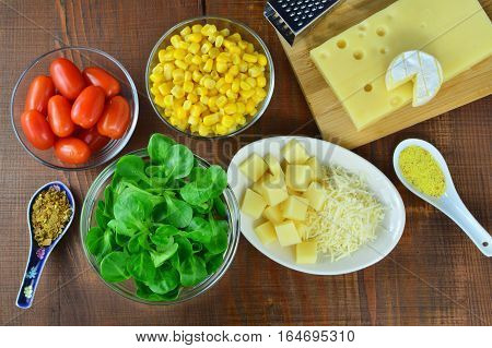Making vegetable salad with sweet corn lamb's lettuce cheese chilly sweet pepper and tomatoes
