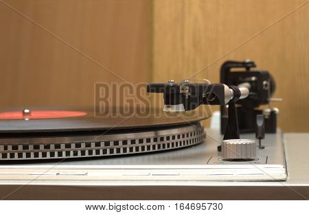 Turntable and vinyl record with red label front view closeup