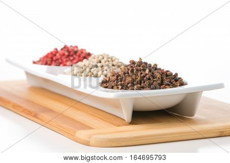 Whole szechuan peppercorns with white and pink peppercorns in the background.