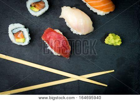 Sushi and Sashimi rolls on a black stone slatter. Fresh made Sushi set with salmon prawns wasabi and ginger. Traditional Japanese cuisine.