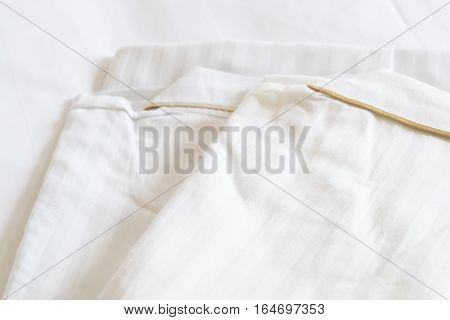 White cotton nightwear folded on bed in the bedroom