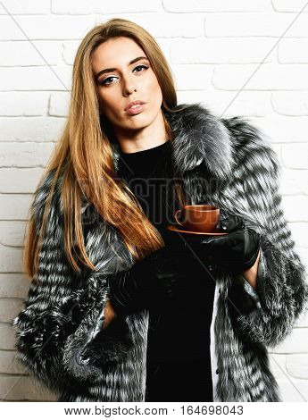 young fashionable sexy pretty rich woman with beautiful long blonde hair in waist coat of grey fur with black leather gloves holding brown ceramic coffee cup on brick wall studio background