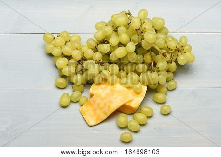 Fresh Grapes And Pieces Of Marbled Cheese