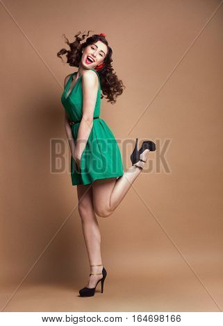 Curly Pin-up girl in green dress having fun and jumping on high heels at light brown rough background.