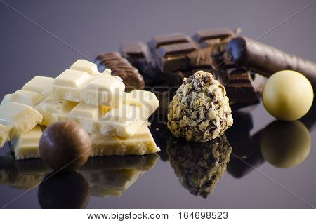 Chocolate assortment on a black background with reflection