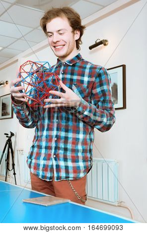 Young smiling man in a plaid shirt standing and holding coloured three-dimensional model of geometric solid.