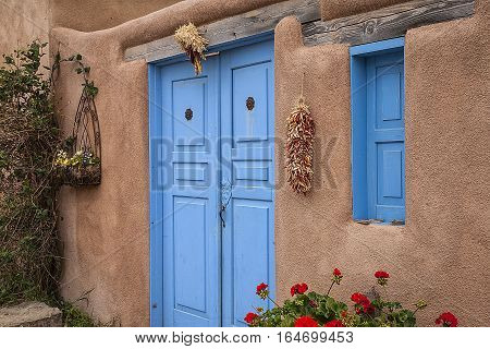 Blue doors of an old adobe house in Taos, New Mexico. Hanging peppers and indian corn. poster