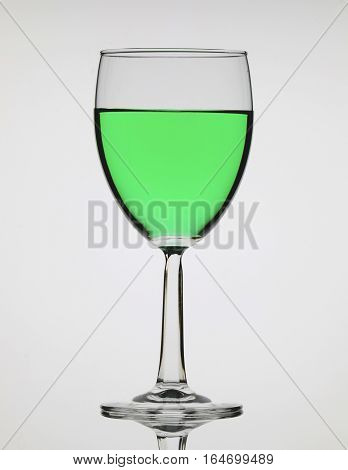 Beautiful and elegant glass with green alcoholic beverage.