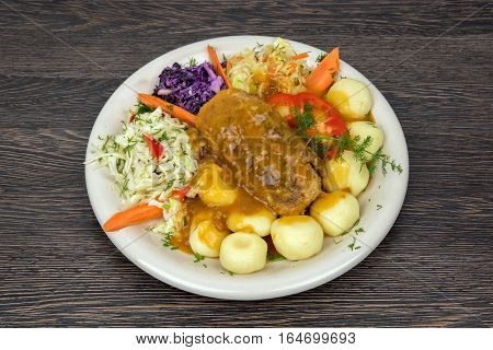 Traditional dish roasted roulade with vegetables and potatoes