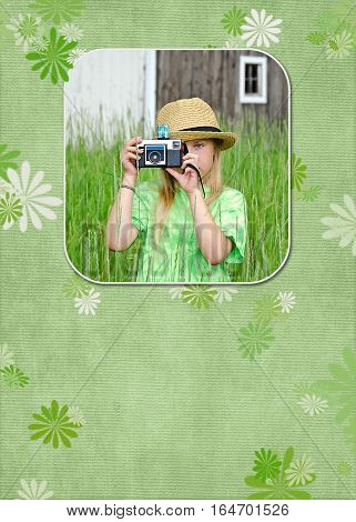 young girl in fedora taking a picture with camera in photo frame on green floral background