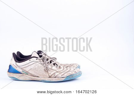 Old blue worn out futsal sports shoes  on white background  isolated