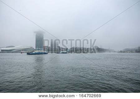AMSTERDAM NETHERLANDS - JANUARY 02 2017: Boats on city channel near pier of Central station in foggy day. January 02 2017 in Amsterdam - Netherland.