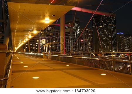 A bridge scene at night with lights in a big city