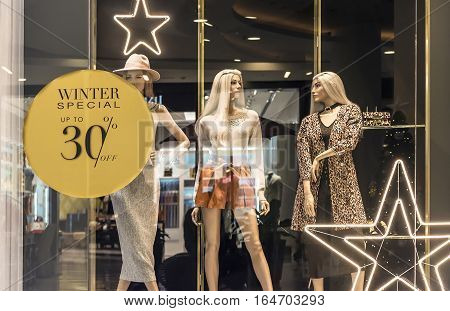 fashion clothes shop display window and sale sign