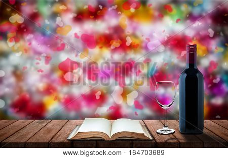 bottle of wine galss of wine and book and on wooden table with colorful heart bokeh background