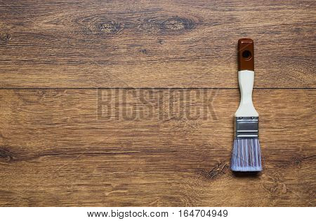 Paintbrush in male hand on a wooden background. Process concept. Tool for painting of walls. Blue paint bristles .Pattern. Vintage background with space