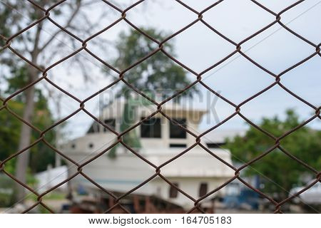 Steel wire mesh fence with blur boat background