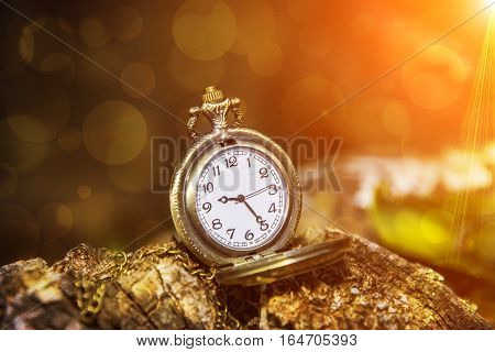 watch locket on the wooden table bokeh background and flare