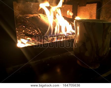 Coffee by the fire with room for copy flames burning in fireplace with hot coffee mug in glow with light beams background image relaxing weekend get away