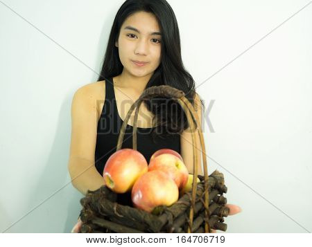Asian woman holding red apple in wooden basket on white background focos on her face take on her side
