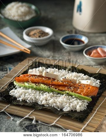 A delicious smoked salmon sushi roll with avocado cream cheese and roasted sesame seeds.