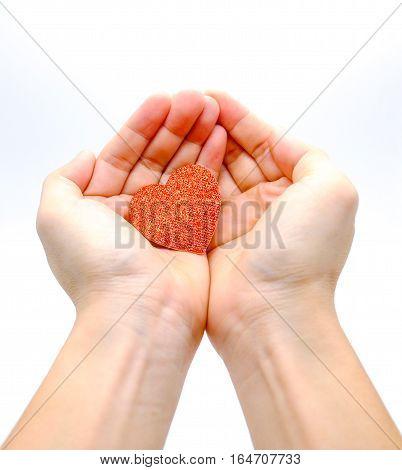 Hands holding glittering heart begging for love