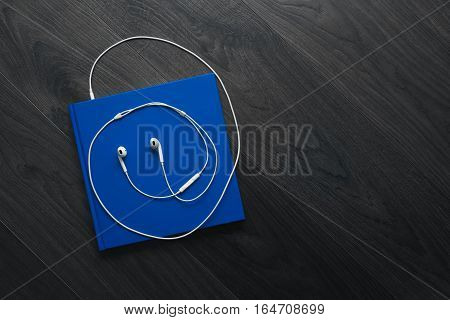 The Blue Book And White Headphones