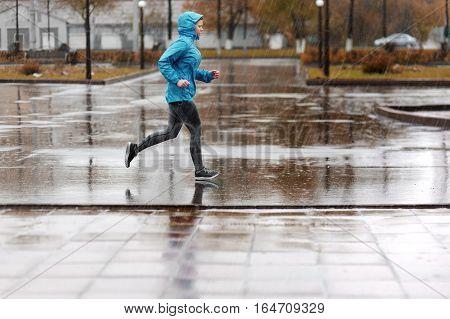 Runner woman running in Park in the rain. Jogging training for marathon. Autumn city rain. poster