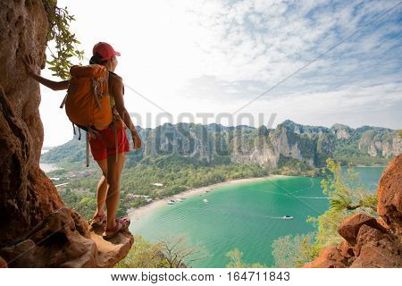 successful woman hiker enjoy the view on mountain cliff