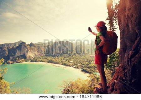 young asian woman hiker taking photo with smartphone at mountain cliff