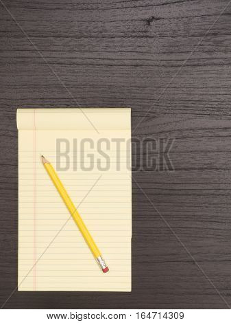 Dark Wood Desk Surface Yellow Notepad Pencil