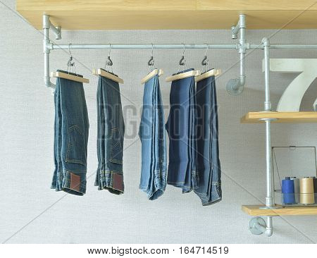 Jeans Hanging In Industrial Style Walk In Closet