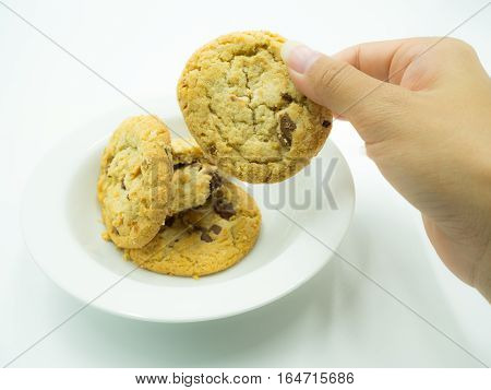 Woman's hand picking up chocolate chip cookies from white plate