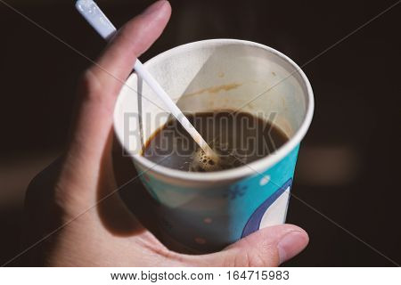 Close focus on black coffee inside paper cup holding by left hand with dark background