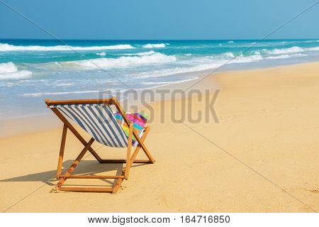 Deckchair with colorful bag on the beach near blue water side - vacation and travel concept.Striped deck chair on the sand.