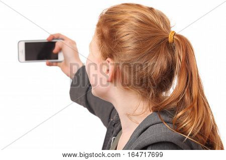 Portrait of a young girl taking a selfie on white background