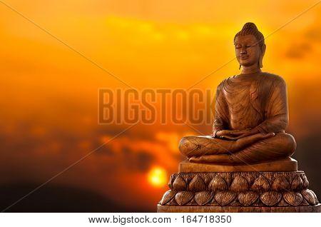 Brown Buddha statue in thailand on sunset background