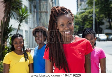 Beautiful african american woman with dreadlocks and other girls in the summer in the city