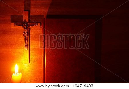 Fire of candle crucifix and Bible in the dark on wood background