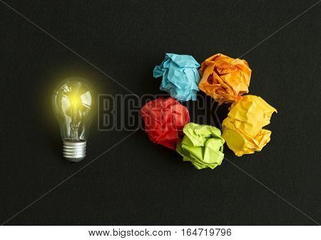 Idea concept with bulb and different colors paper wads on black background
