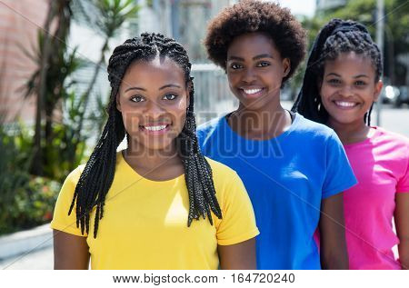 Three cheerful african american woman standing in line in the summer in the city