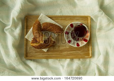 Bagel and cup of turkish tea on the wood tray with Istanbul picture on the bedcover tod down view