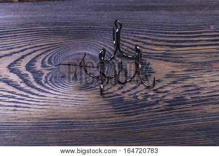 fishing hooks on dark wooden background, close up