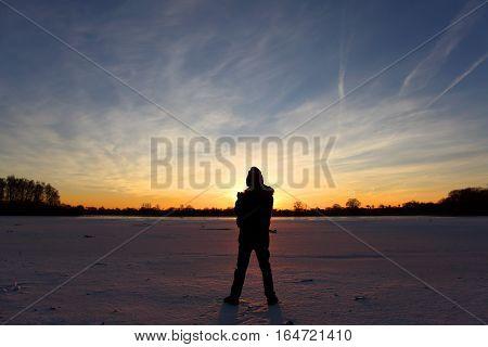 Young boy at lake at orange sunset