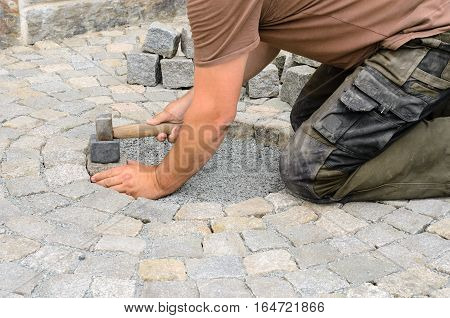 Construction worker installing stone blocks on pavement