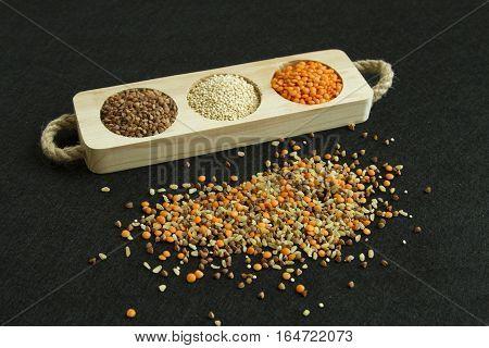 Heap from four different groats: buckwheat lentil quinoa bulgur on black background