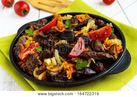 Pieces of roast duck goose (meat liver heart) with vegetables (onion carrot tomato) with spices on a round cast-iron frying pan on a green napkin.