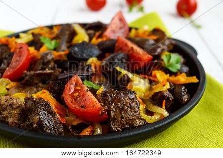 Pieces of roast duck goose (meat liver heart) with vegetables (onion carrot tomato) with spices on a round cast-iron frying pan on a green napkin. Close up